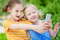 Twee leuke kleine zusters die openlucht mobiel spel op hun slimme telefoons spelen Stock Afbeeldingen