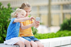Twee leuke kleine zusters die openlucht mobiel spel op hun slimme telefoons spelen Stock Foto