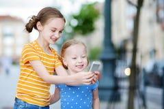 Twee leuke kleine zusters die openlucht mobiel spel op hun slimme telefoons spelen Royalty-vrije Stock Foto