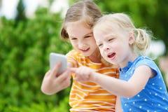 Twee leuke kleine zusters die openlucht mobiel spel op hun slimme telefoons spelen Royalty-vrije Stock Fotografie