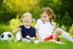 Twee leuke kleine zusters die pret hebben die een voetbalspel op zonnige de zomerdag spelen Sportactiviteiten voor kinderen royalty-vrije stock foto
