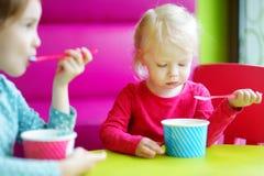 Twee leuke kleine zusters die roomijs samen eten Stock Foto's