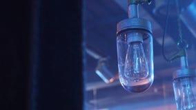 Twee leuke lampen met lang lightbulbs opgezet aan plafond met glas plafond stock footage