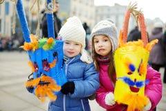 Twee leuke meisjes die angstaanjagende maskers dragen tijdens de viering van Uzgavenes, een Litouws jaarlijks volksfestival plaat stock foto