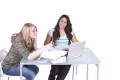 Twee leuke meisjes die bij hun bureaus bestuderen Stock Fotografie