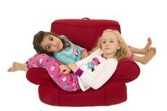 Twee leuke meisjes die de winterpyjama's het ontspannen dragen Stock Afbeelding