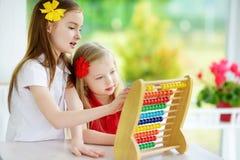 Twee leuke meisjes die met telraam thuis spelen Grote zuster die haar sibling onderwijzen om te tellen Slim kind die leren te tel Royalty-vrije Stock Fotografie