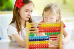 Twee leuke meisjes die met telraam thuis spelen Grote zuster die haar sibling onderwijzen om te tellen Slim kind die leren te tel Stock Afbeeldingen