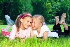 Twee leuke meisjes die op het gras lachen Stock Foto