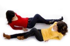 Twee leuke meisjes die tegengesteld aan elkaar liggen stock afbeelding