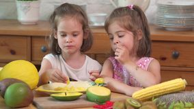 Twee leuke meisjes lachen en eten een sappige gele mango stock video