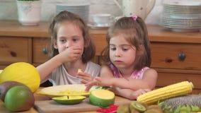 Twee leuke meisjes lachen en eten een sappige gele mango stock videobeelden