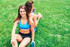 Twee leuke sportieve meisjes die na training ontspannen openlucht stock afbeeldingen