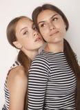 Twee leuke tieners die die pret hebben samen op wit wordt geïsoleerd Royalty-vrije Stock Foto