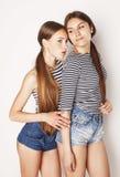 Twee leuke tieners die die pret hebben samen op wit wordt geïsoleerd Royalty-vrije Stock Afbeelding