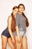 Twee leuke tieners die die pret hebben samen op wit wordt geïsoleerd Stock Fotografie