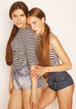 Twee leuke tieners die pret samen op wit hebben Stock Afbeelding