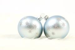 Twee lichtblauwe en zilveren Kerstmisballen op witte bontachtergrond Royalty-vrije Stock Fotografie