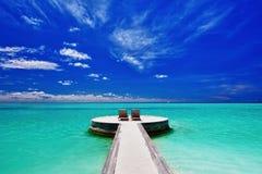 Twee ligstoelen bij het overweldigen van tropisch strand Royalty-vrije Stock Foto
