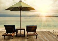 Twee ligstoelen en umberella op oceaanstrand bij zonsondergang stock foto
