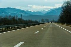 Twee lijn brede weg op een bewolkte de winterdag Stock Fotografie