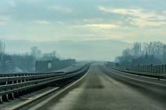 Twee lijn brede weg op een bewolkte de winterdag Royalty-vrije Stock Fotografie