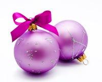 Twee lilac Kerstmisballen met geïsoleerd lint Stock Afbeeldingen