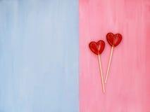 Twee lollys op roze en blauwe achtergrond Het concept van de liefde Rood nam toe Royalty-vrije Stock Foto