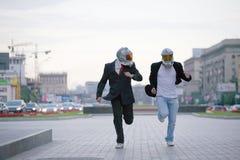 Twee lopende zakenlieden met gasmaskers stock foto's