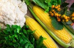 Twee maïskolven met groenten op hout Stock Foto's