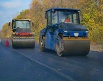 Twee machines die van de asfaltbetonmolen op nieuwe weg rollen royalty-vrije stock foto