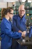 Twee machinisten die aan machine werken Stock Foto
