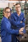 Twee machinisten die aan machine werken stock afbeelding