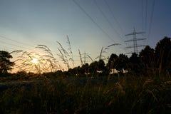 Twee machtspolen en zonnestralen van een zonsondergang royalty-vrije stock afbeelding