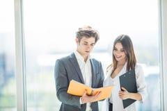Twee managers die winst bespreken Groep bedrijfsmensen die in bureau samenwerken die over notitieboekje bespreken Jong opstarten Stock Foto's