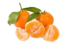 Twee mandarines of mandarijnen met bladeren en gepelde  Royalty-vrije Stock Afbeeldingen