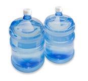 Twee mandeflessen met drinkwater Stock Afbeeldingen