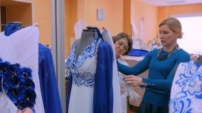 Twee manierontwerpers die met nieuwe model het maken kleding aan ledenpop werken stock footage