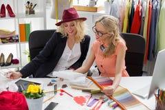 Twee manierontwerpers die schets op hun kantoor bekijken royalty-vrije stock afbeelding