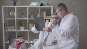Twee mannelijke artsen die röntgenstraal in het bureau van moderne kliniek controleren Concept geneeskunde, gezondheidszorg en me stock footage