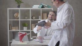 Twee mannelijke artsen die röntgenstraal in het bureau van moderne kliniek controleren De mensen bereiken consensus en schokhande stock video