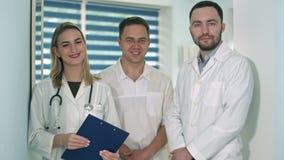 Twee mannelijke artsen en vrouwelijke arts die met stethoscoop aan de camera glimlachen stock footage