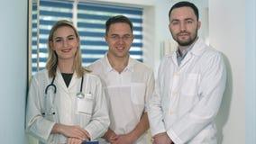 Twee mannelijke artsen en vrouwelijke arts die met stethoscoop aan de camera glimlachen Royalty-vrije Stock Afbeeldingen