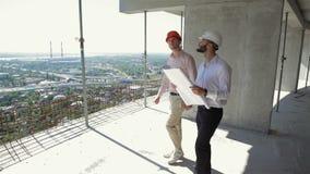 Twee mannelijke bouwers die door het gebouw in aanbouw lopen stock videobeelden