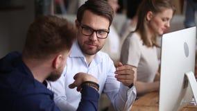 Twee mannelijke collega's die bij bureau spreken samenwerken die samenwerken stock videobeelden