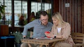 Twee mannelijke en vrouwelijke vrienden zitten bij lijst in koffie, gebruikend smartphones stock video