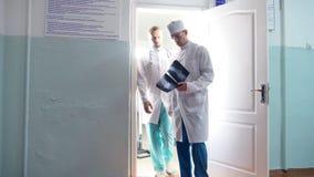 Twee mannelijke Kaukasische artsen komen uit kabinet en het beeld van meningsmri, die iets op röntgenstraal aan elkaar, recentere stock video