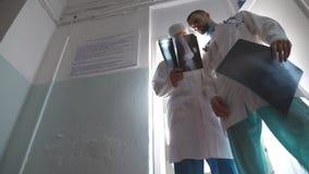 Twee mannelijke Kaukasische artsen komen uit kabinet en het beeld van meningsmri, die iets op röntgenstraal aan elkaar, recentere stock footage