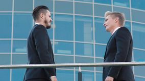 Twee mannelijke medewerkers die in openlucht over hun zaken spreken stock video
