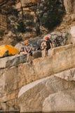 twee mannelijke reizigers in beschermende helmen die dichtbij tent en fietsen op rotsachtig rusten royalty-vrije stock afbeeldingen